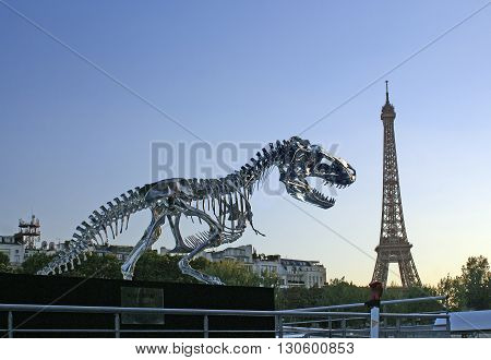 PARIS FRANCE - SEPTEMBER 22 2013: Sculpture Tyrannosaur in Paris on the river Seine on background of the Eiffel Tower. Sculptor Philippe Pasqua