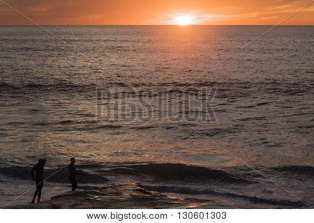 Two male surfers in Windansea beach during red sunset in San Diego, California