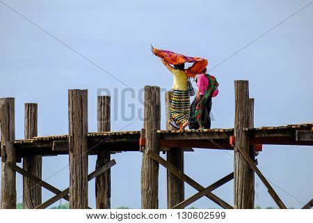 Two Asian women in colorful clothes walking on wooden bridge Amarapura Mandalay Myanmar