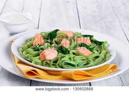 Salmon and Spinach Fettuccine pasta on white dishes and table napkin. cream sauce in a gravy boat on a white table italian style studio lights close-up