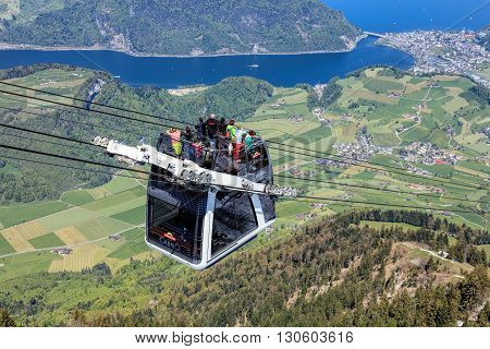 Mt. Stanserhorn, Switzerland - 7 May, 2016: people in a gondola of the Stanserhorn Cabrio cable car. Stanserhorn Cabrio is the the world's first double deck open top cable car it carries 60 passengers per cabin with room for 30 on the open deck.
