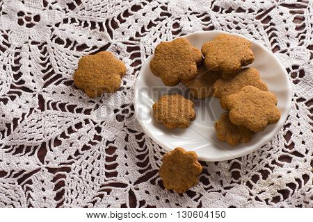 Tasty honey cookies are on crochet tablecloth.