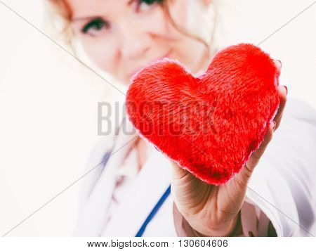Love from working and helping people. Mid age blonde doctor in white medical apron with heart. Enjoy work concept. Isolated on white.