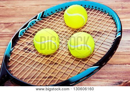 Tennis game. Tennis ball and racket on wooden background. Vintage retro picture.