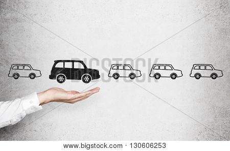 Man's hand choosing black car sketch over row of white cars on concrete wall. Concept of choice