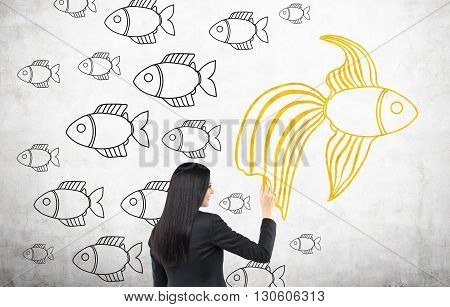 Different direction concept with businesswoman drawing goldfish sketch on concrete wall