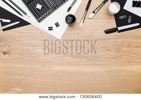 Top view of wooden tabletop with drawing tools and stationery items. Mock up