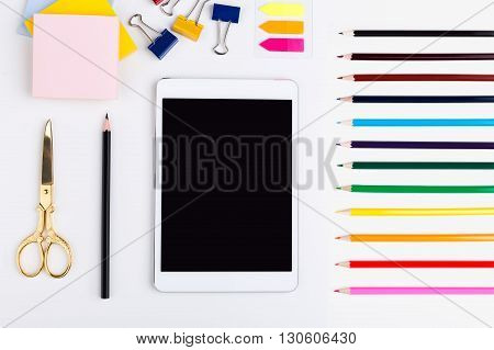 Top view of blank tablet screen colorful pencils golden scissors stickers and pegs on white surface. Mock up