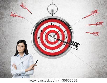 Time management and targeting concept with abstarct dartboard clock and businesswoman on concrete background