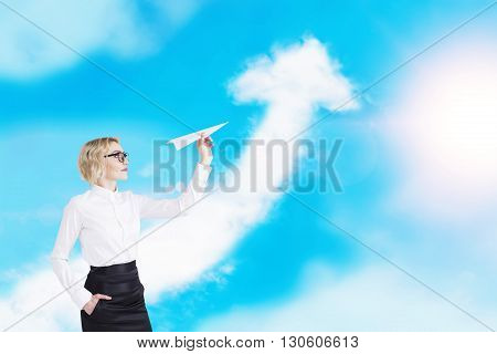 Success concept with businesswoman playing with paper plane on sky background with upward arrow cloud