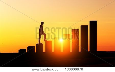 Success concept with businessman silhouette climbing chart bars at sunset