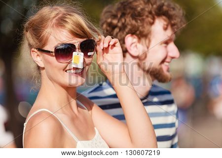 Summer holidays shopping concept. Young couple of tourists buying new sunglasses in street stall outdoor
