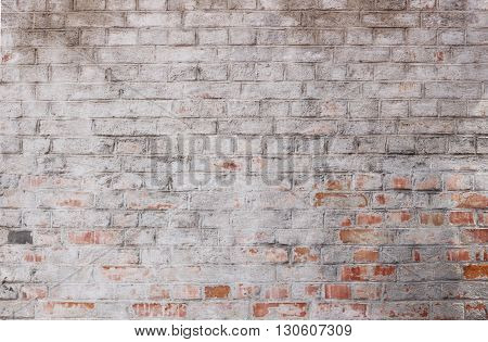 background - old brick wall with red white painted and plastered bricks
