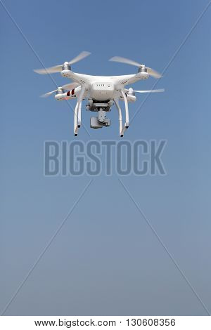 KAGAWA, JAPAN - MAY 06, 2016: White remote controlled Drone Dji Phantom 3 equipped with high resolution video camera hovering in air with beach and clear blue sky in the background