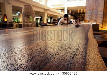 Honolulu, Hawaii, USA - Dec 15, 2015: Lounge area of the Waikiki Beach Marriott Resort and Spa Hotel. This is a public area. Image features warm color and a person seated at a long wooden table reading. Image emphasizes on the textured table top.