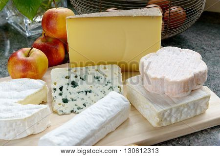 a tray with different French cheeses with apples