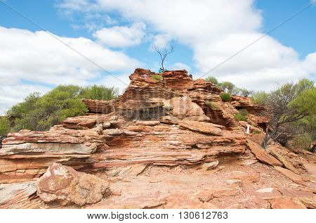 Unique red sandstone bluff under a blue sky with clouds in Kalbarri National Park in Kalbarri, Western Australia.