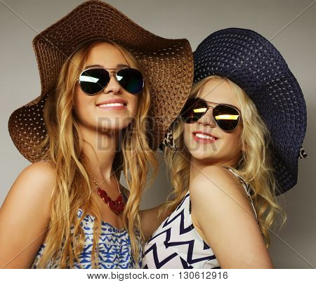 girls friends wearing summer dress and straw hats laughing and hug