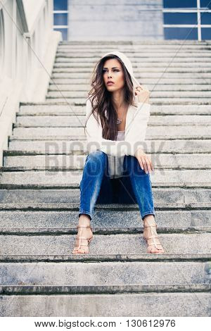 urban young woman sit on stairs in blue jeans high heel sandals and white sweater with hood full body shot