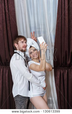 Husband and wife make fun selfie. Girl with a towel over his head. Marital time. After a night in a hotel. Fooling around together.