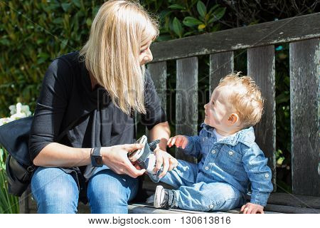 young mother helping her cute toddler boy putting his shoe on enjoying time together in the park