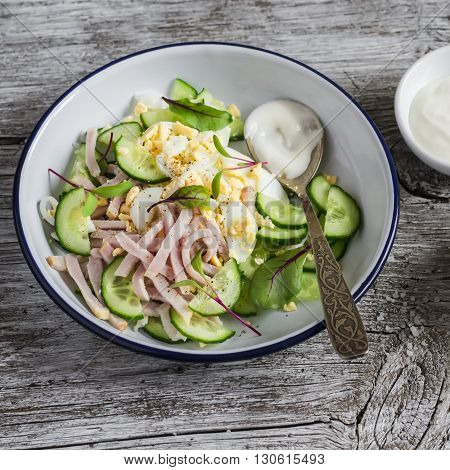 Easy and fast salad with smoked turkey cucumber and boiled egg on a wooden background. Healthy food