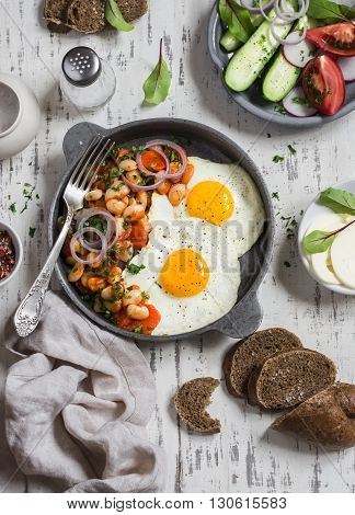 Delicious breakfast or snack - a fried egg beans in tomato sauce with onions and carrots fresh cucumbers and tomatoes homemade rye bread on light wooden background