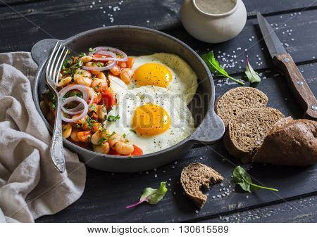 Fried egg beans in tomato sauce with onions and carrots fresh cucumbers and tomatoes homemade rye bread - delicious breakfast or snack on dark wooden background