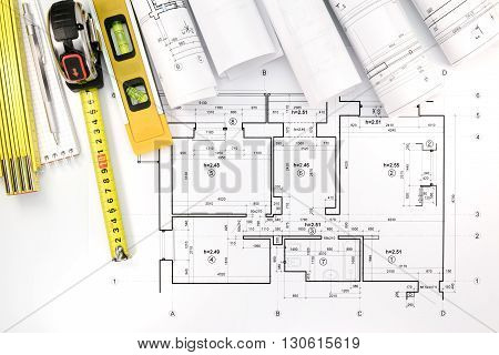 Rolls Of Architectural Blueprints And House Plan With Engineering Tools