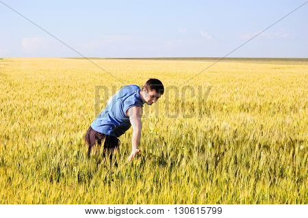 The guy wheat ears touches wheat ears with his hand