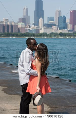 A young couple in a romantic and sensual mood on a sunny day standing by the riverside. On the background, several highrise buildings and the clear blue sky is seen.