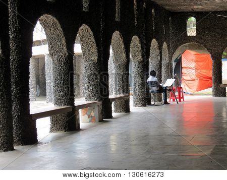 Chandigarh-Aug 02: A sketch artist sitting alone at the end of hall, Rock Garden Aug 02, 2015 in Chandigarh, India, Asia.