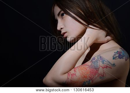 Beautiful asian woman with tattoo on her arm and shoulderdark background