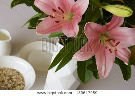 Pink lillies and green leaves at the breakfast table.