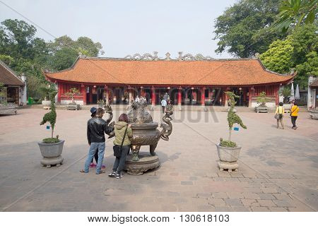HANOI, VIETNAM - JANUARY 09, 2016: Tourists view ancient bronze incense burner at the Temple of Literature. Historic landmark of the city Hanoi, Vietnam