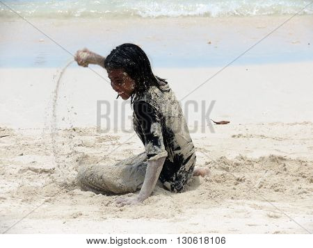 Andaman-Apr 15: A girl playing with sand on the beach, Andaman Apr 15, 2012 in Andaman and Nicobar Islands, India, Asia.