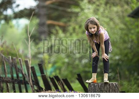 Ten years girl with headphones standing on a stump near the country house.