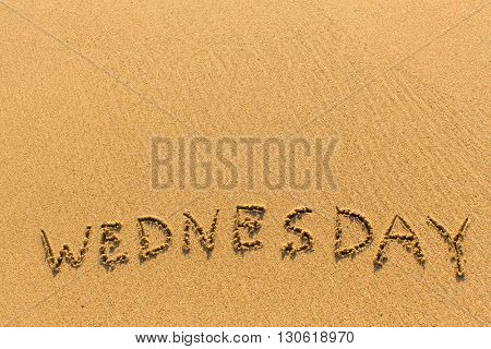 Wednesday - written by hand on a golden beach sand.