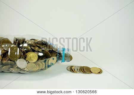Saving Thai baht coins in big recycle bottle on white background