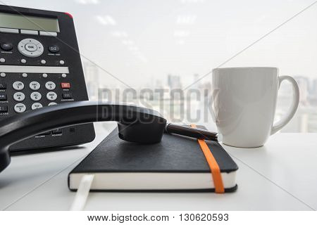 IP Phone and a cup of coffee and black notebook