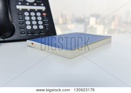 IP Phone and blue notebook on the white table - Technology of communication