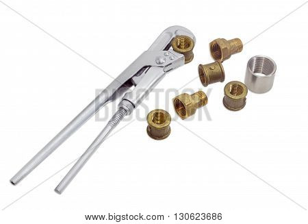 Plumber wrench and several brass and steel pipe couplings and adapters on a light background