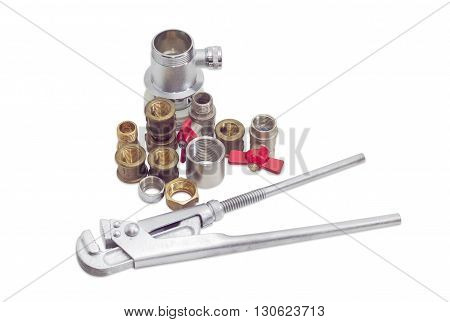 Plumber wrench and several brass and steel pipe couplings adapters nuts ball valves and trap on a light background