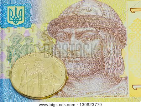 Coin one Ukrainian hryvnia with depicting of Kievan Rus Prince Volodymyr the Great against a background of fragment banknote one hryvnia