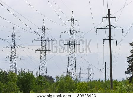 One overhead power line with reinforced concrete poles and several overhead power lines with steel lattice structures transmission tower against the backdrop of an overcast sky