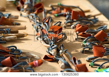 Street stall with a large group of handmade slingshots for sale