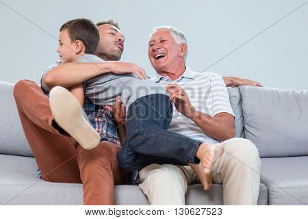 Father sitting on sofa with grandfather and embracing son in living room