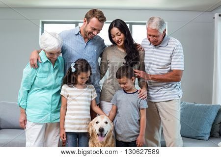 Family standing together with dog in living room