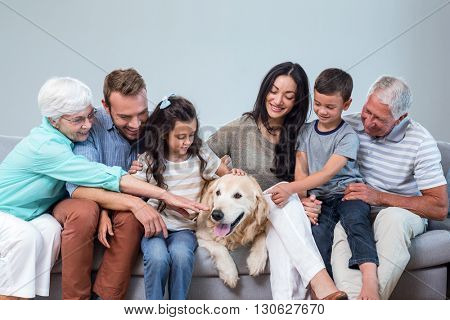 Family sitting on sofa with dog in living room