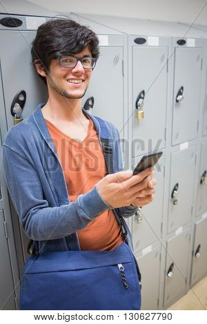 Portrait of smiling student standing in locker room and using mobile phone